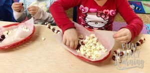 Popcorn and Cranberry Stringing Measurement Activity for Preschool and Kindergarten. Fun math activity for learning measurement, counting, and fine motor skills! #mathcenter #measurement #funearlylearning